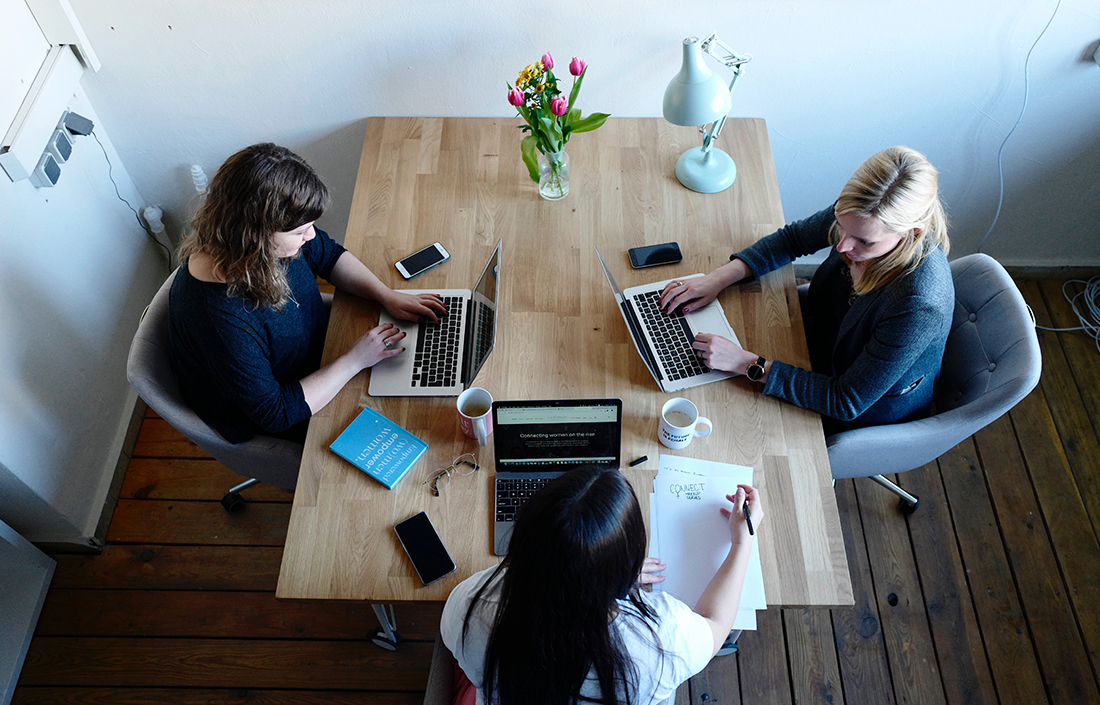 Three women in relaxed meeting with their laptops on wooden table