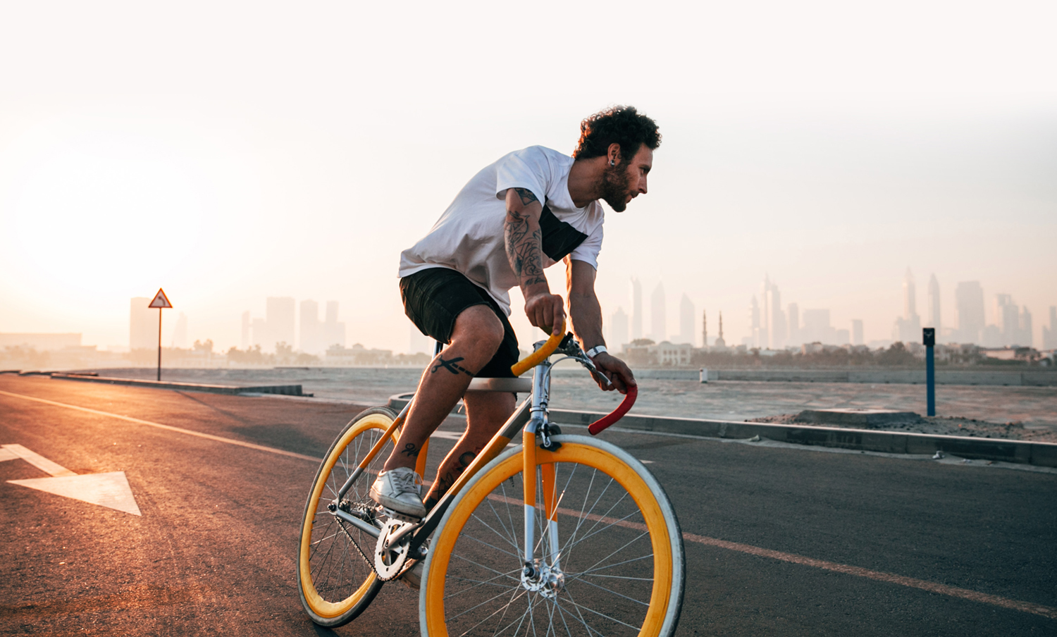 Man cycling in shorts while the sun rises